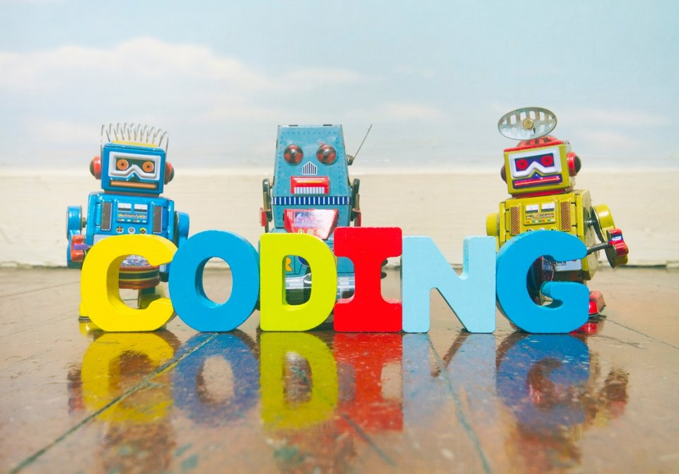 Colorful letters composing the word coding with some colorful robots in the background